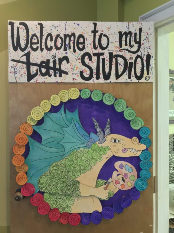 """A door with a hand drawn dragon with the sign above that reads, """"Welcome to my Lair Studio."""""""